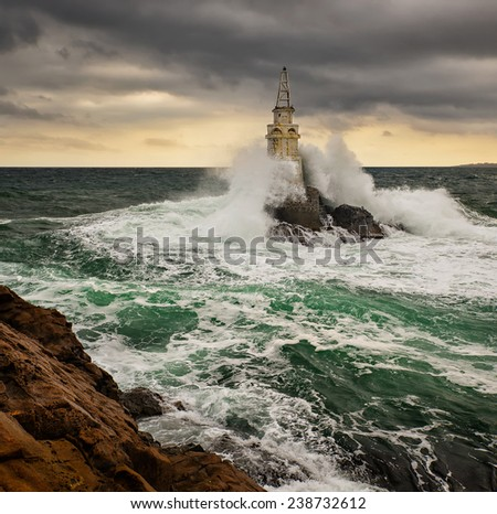 Lighthouse in a stormy sea - stock photo