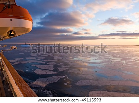 Lighthouse in the Arctic Sea at sunset. View from the boat - stock photo