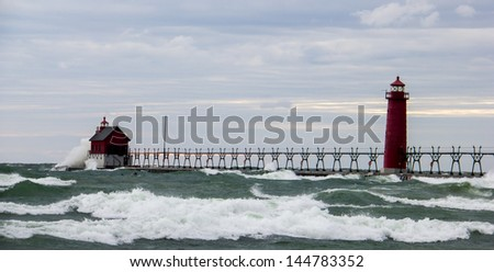 Lighthouse near Grand Haven, MI being pounded by high waves - stock photo