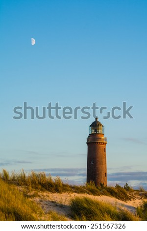 lighthouse of Darsser Ort in Germany and the moon at sundown - stock photo