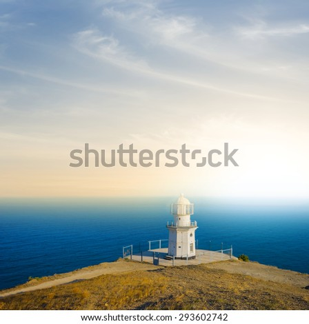 lighthouse on a hill above a sea - stock photo