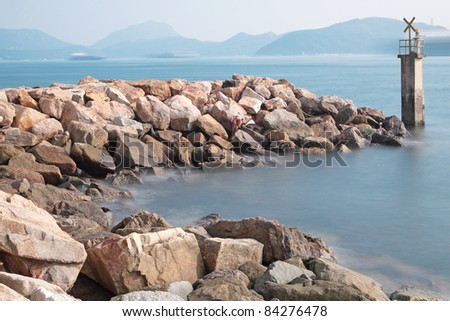 Lighthouse on a Rocky Breakwall: A small lighthouse warns of a rough shoreline. - stock photo