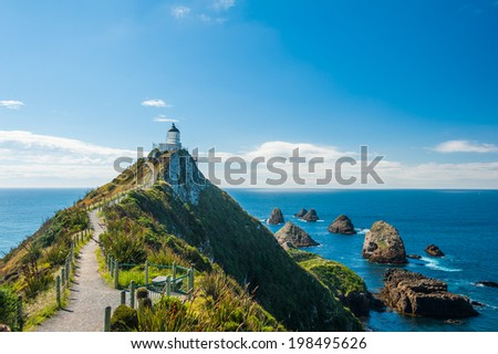 Lighthouse on Nugget Point. It is located in the Catlins area on the Southern Coast of New Zealand, Otago region. The Lighthouse is surrounded by small rock islands, nuggets - stock photo