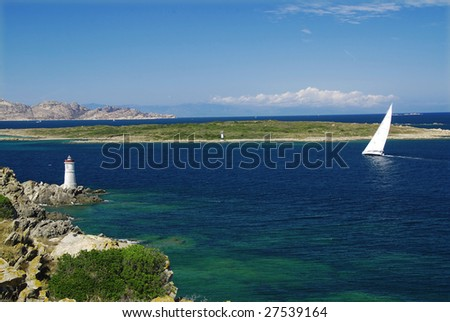 Lighthouse on Sardinian rocks and a yacht sailing in the sea - stock photo