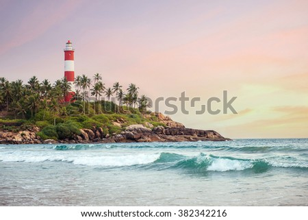 Lighthouse on the cliff with sunset on background surrounded by palm trees and big sea waves on the Kovalam beach. Kerala, India - stock photo