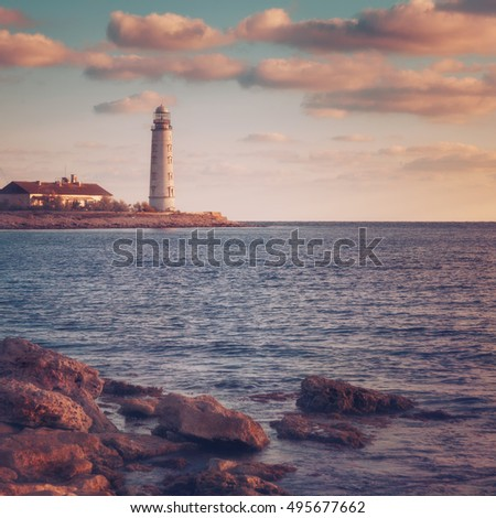 Lighthouse on the coast on the background of sky with clouds