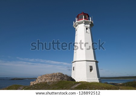 Lighthouse on the rocky area located on the Atlantic Ocean - stock photo
