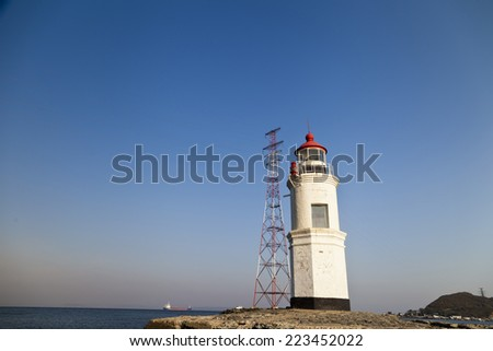 Lighthouse on the shore of the open sea in front of the harbor - stock photo