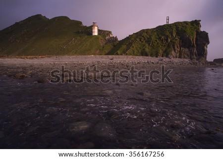 Lighthouse on the slope of the cape. The Sea of Okhotsk. Koni peninsula. Cape Taran. Magadan Region. Russia. - stock photo