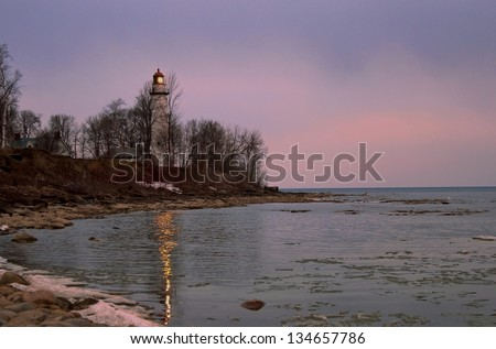 Lighthouse Reflections. Twilight captures the reflection of the lighthouse beacon. Lighthouse County Park. Port Hope, Michigan. - stock photo
