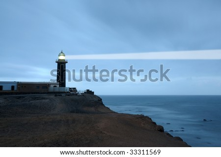Lighthouse searchlight beam through foggy air. Punta de Jandia, Fuerteventura, Spain