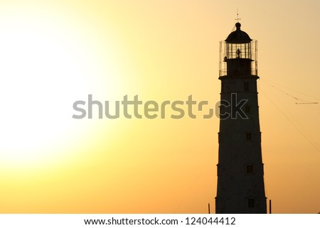 Lighthouse silhouette among golden sunset sea