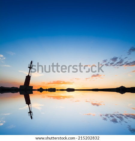 lighthouse silhouette reflected in the water - stock photo
