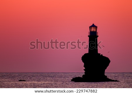 Lighthouse Tourlitis of Chora in Andros island and seagulls, Cyclades, Greece