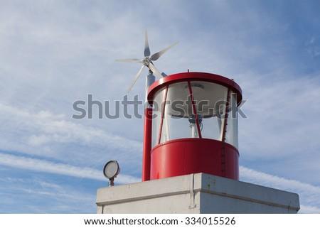 Lighthouse wind a mall windturbine on a sunny day with blue sky. - stock photo