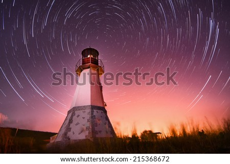 lighthouse with beam to night sky at background stars trails - stock photo