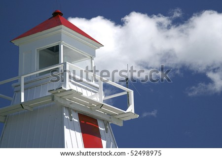 Lighthouse With Clouds On Great Lakes Shore - stock photo