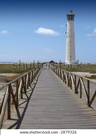 Lighthouse with footbridge at the beach of jandia fuerteventura, spain
