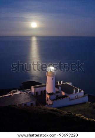 Lighthouse with Full Moon Reflecting in the Sea on the Isle of Man - Vertical Composition - stock photo