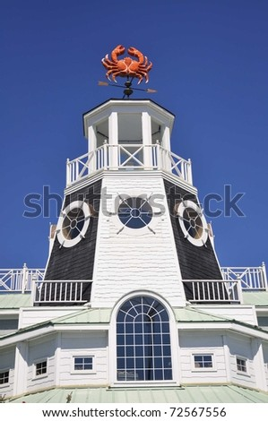 Lighthouse with fun Crab weather vane reaching into a beautiful blue sky
