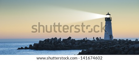 Lighthouse with light beam at sunset - stock photo
