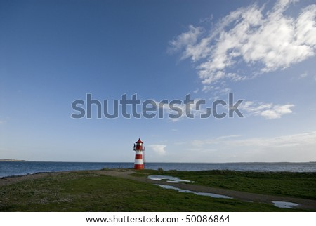 Lighthouse with man on balcony in middele of nowhere - stock photo