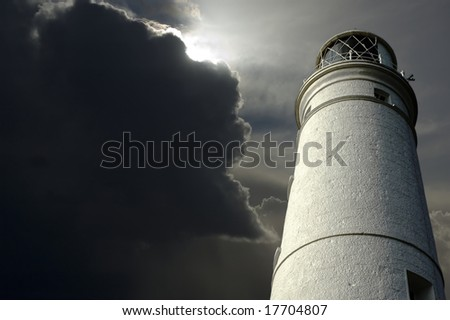Lighthouse with storm clouds approaching. - stock photo