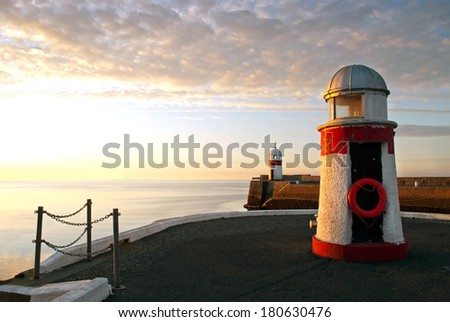 Lighthouses on breakwater wall with calm sea during sunrise.  Tranquil scene on Isle of Man - stock photo