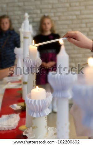 Lighting a series of tall slender candles - stock photo