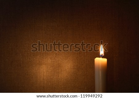 Lighting candle against canvas background with free space for text - stock photo