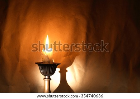 Lighting candle in candlestick on craft paper background - stock photo