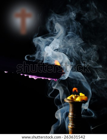lighting candle to candle on smoke with blur cross backdrop