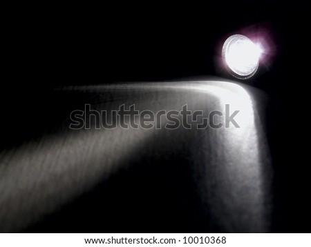 Lighting flashlight at dark night with light like arrow - stock photo