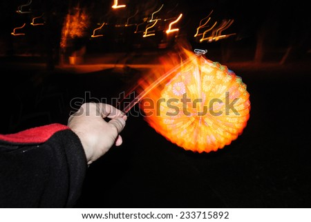 Lighting paper lantern in hand with illusion of motion and flame - stock photo