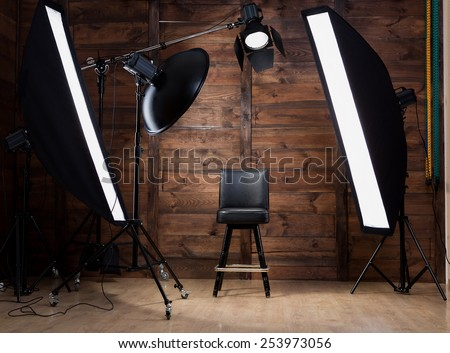 Lighting set up in photostudio with wooden background - stock photo