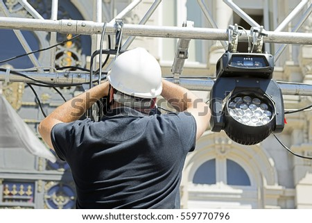 lighting technician. lighting technician intstalling professional equipment for concert stage installation with led lights and projectors