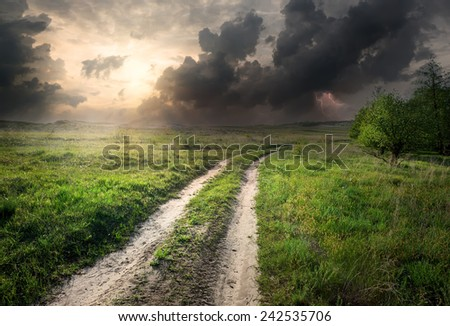 Lightning and storm clouds over country road - stock photo