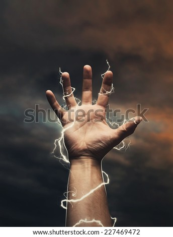 Lightning around men's hand - stock photo