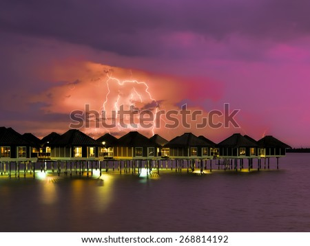 Lightning colouring the sky over water villas at night - stock photo