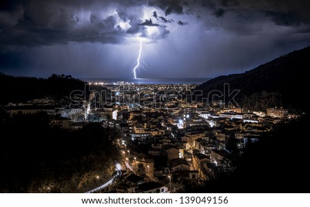 Lightning in the sea in front of the city in Italy - stock photo
