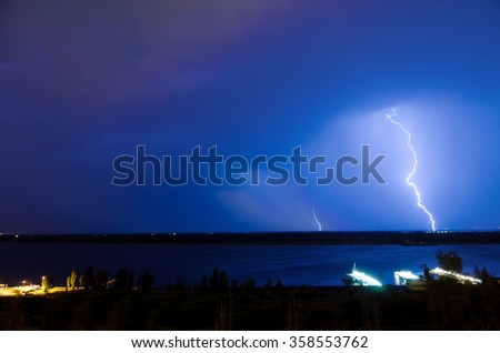 Lightning over night river in the blue sky - stock photo