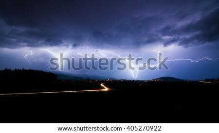 Lightning storm over city in purple light - stock photo