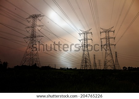 Lightning strike at an electric power line across a rural landscape.  - stock photo