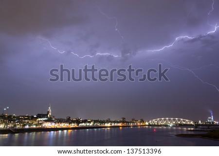 Lightning strike at night over the city of Nijmegen, the Netherlands - stock photo