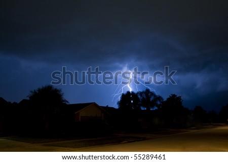 Lightning strike behind a tree in a local neighborhood - stock photo