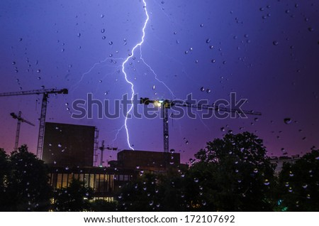 Lightning strike in a construction area viewed through glass with rain drops.