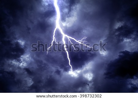 Lightning strike on the dark cloudy sky. - stock photo