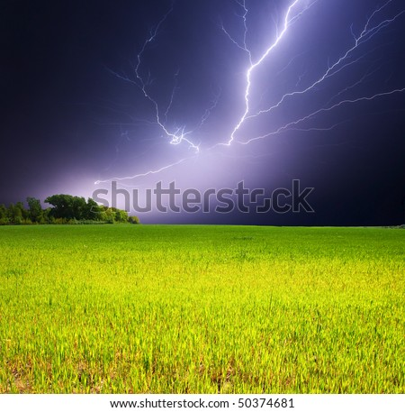 Lightning strike over a field - stock photo
