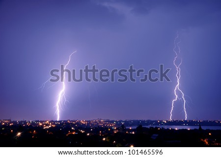 Lightning strike over dark blue sky in night city - stock photo