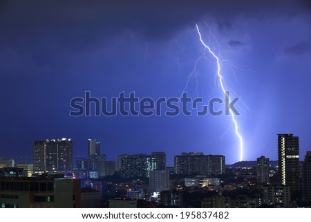 Lightning thunderbolt hitting a hill beyond the city limits. Intense flash illuminating the cityscape in a blue light.